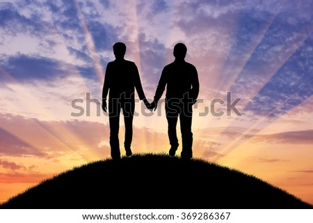 Concept of gay people. Silhouette happy gay men walking holding hands at sunset