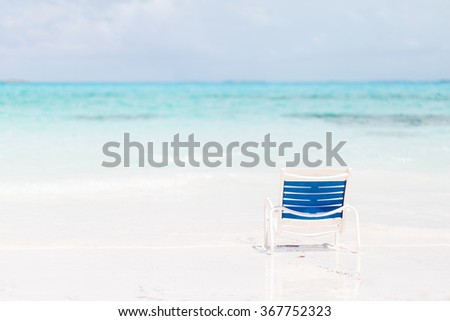 Concept of getaway. Chair on the tropical, white sandy beach on Bahamas with turquoise water.