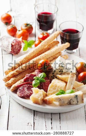 Concept of italian antipasto with cheese and sausage, selective focus