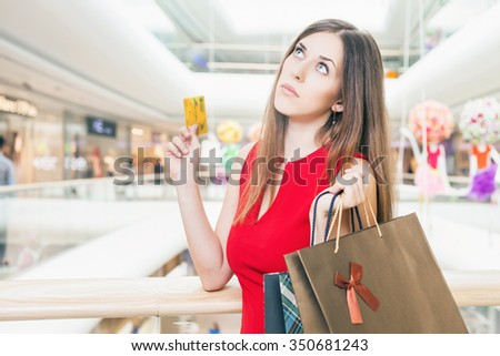 Concept of shopping and payment by plastic card at big mall center. Fashion successful woman holding credit card and bags with purchases. Looking up. She is happy and awesome buyer!