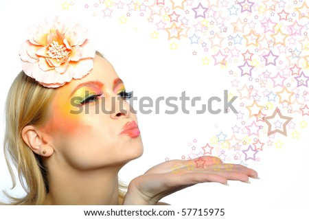 Concept of summer woman with creative eye make-up in yellow and green tones bloving stars from her hand. copy-space