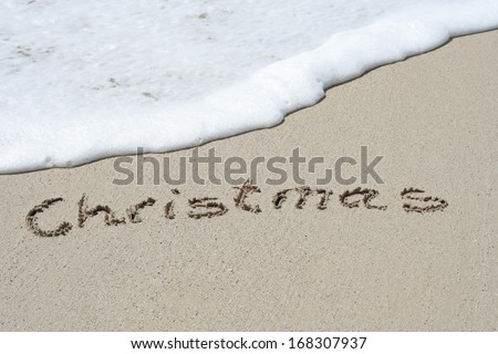 Concept or conceptual hand made or handwritten Christmas text in sand on a beach in an exotic island