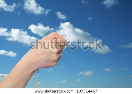 Concept or conceptual human or man hand holding a internet or data cable in clouds over the blue sky, as a metaphor for plug connection technology share network mobility connectivity or communication