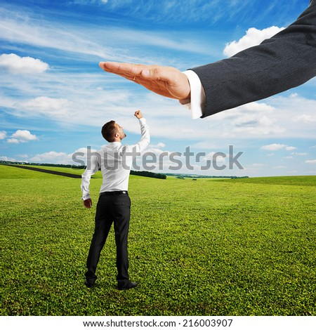 concept photo of conflict between subordinate and boss. displeased businessman looking up at big palm of his boss and showing fist. bright photo at outdoor