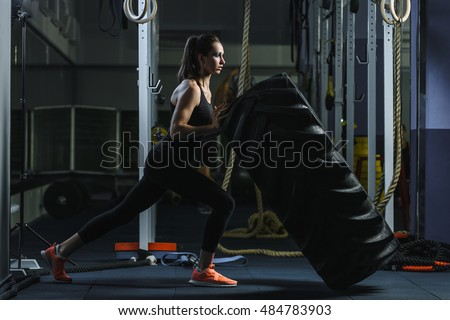 Concept: power, strength, healthy lifestyle, sport. Powerful attractive muscular woman CrossFit trainer doing giant tire workout at the gym
