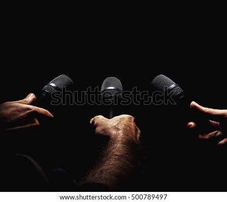 Conceptual composition about journalism, three microphones in hands ready to interview somebody.