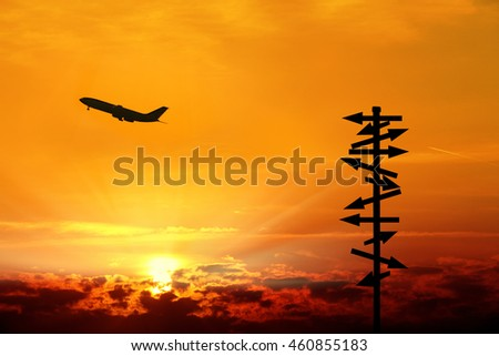 conceptual image of commercial airplane and directional signs over sunset