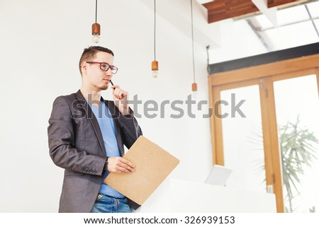 conceptual portrait of a man thinking of new ideas for business in office interior