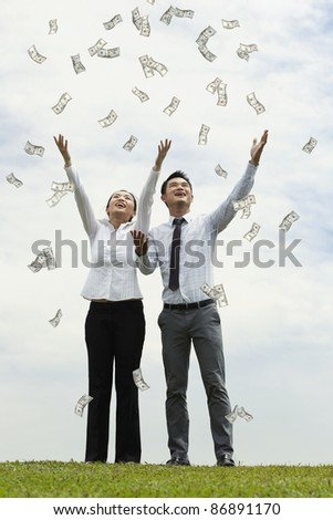 Conceptual Stock image of a man & woman standing with open arms amidst falling money