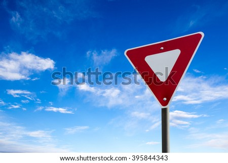 Conceptual yield sign against a blue cloudy sky.