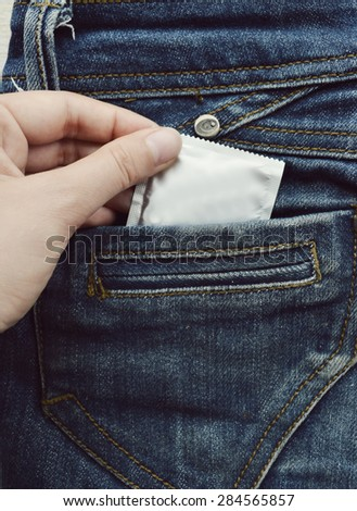 condom in blue jeans pocket,Protect yourself Use a condom.a woman holding a condom ,ready for use