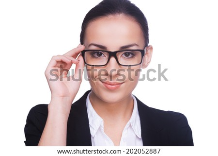 Confident and successful. Confident young woman in formalwear adjusting her eyeglasses and looking at camera while standing isolated on white
