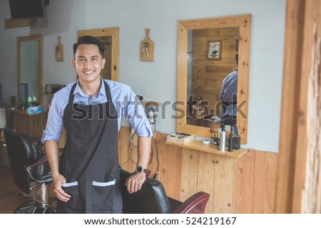 Confident barber expert. Young man looking at camera and smiling standing at barbershop