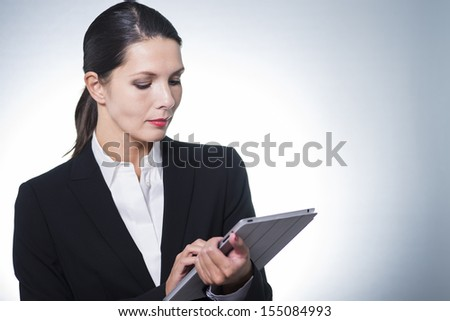 Confident business manageress working on a tablet computer as she stands looking at the tablet with a serious thoughtful expression, studio portrait with copyspace