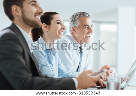 Confident business people team having a meeting in the office and smiling, office interior on background