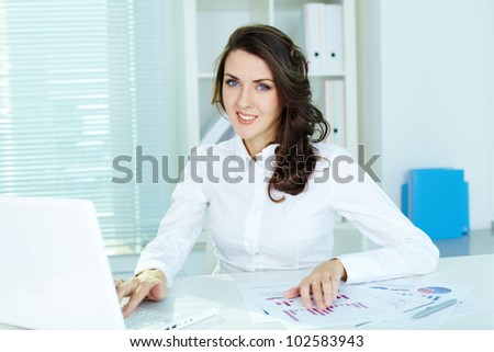 Confident business woman looking at camera in the middle of the work