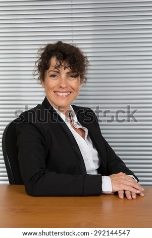 Confident business woman smiling at her office