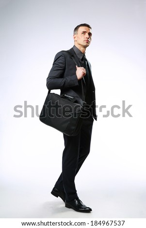 Confident businessman with bag looking up over gray background