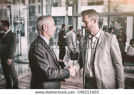 Confident businessmen shaking hands in office