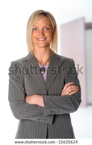 Confident businesswoman with arms crossed in boardroom
