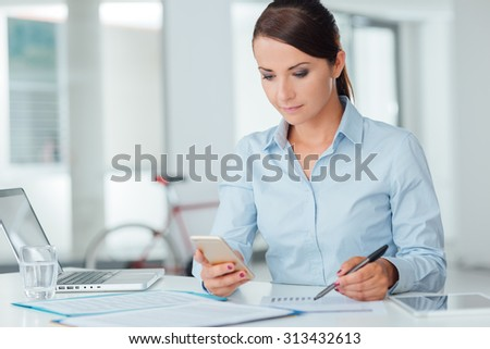 Confident businesswoman working at office desk and using a touch screen smart phone, room interior on background