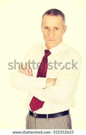 Confident mature businessman with folded arms.