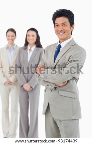 Confident smiling businessman with his employees behind him against a white background