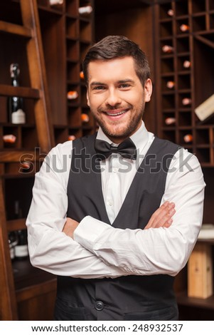 Confident sommelier. Confident male sommelier keeping arms crossed and smiling while standing near the wine shelf