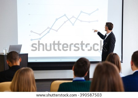 Confident speaker giving public presentation using projector in conference room