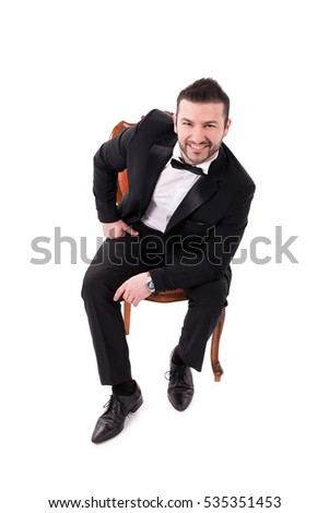 Confident Successful Smart  Looking Man Smiling, sitting on chair and  wearing black tuxedo, isolated on white background