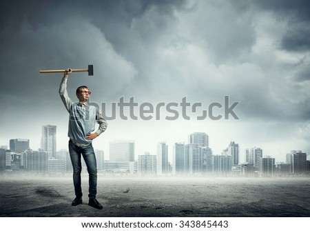 Confident teenager boy holding hammer in hand above head