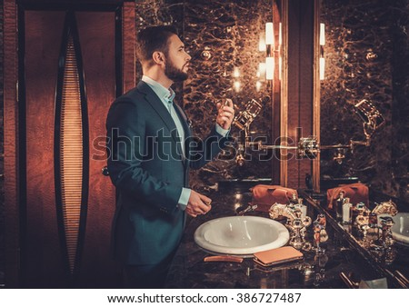 Confident well-dressed man using perfume in luxury bathroom interior.