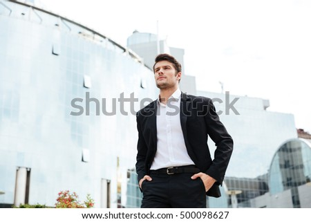 Confident young businessman in suit walking in the city