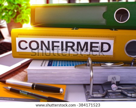 Confirmed - Yellow Ring Binder on Office Desktop with Office Supplies and Modern Laptop. Confirmed Business Concept on Blurred Background. Confirmed - Toned Illustration. 3D Render.
