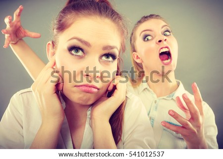 Conflict, bad relationships, friendship difficulties. Two young women having argument. Angry fury girl screaming at her friend or younger sister, female closing his ears, not listening