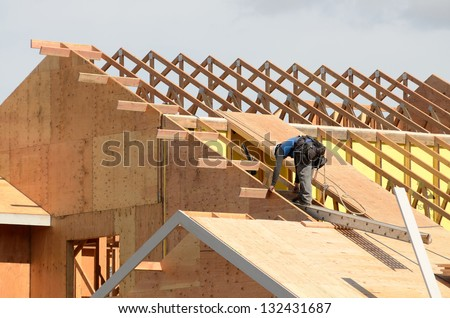 Builder Trying Board Attic Floor Joists Stock Photo