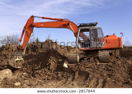 Construction digger on a mound of earth