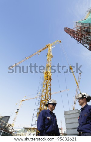 construction engineers, workers, giant cranes, scaffolding and machinery in background,