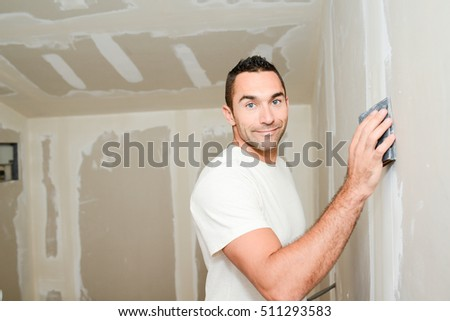 construction industry worker with tools plastering walls and renovating house in construction site