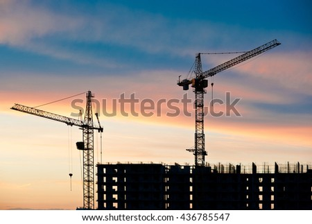 construction site and cranes against sunset sky background