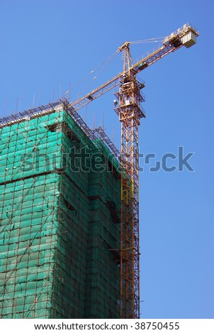 Construction site with big yellow cranes and blue sky