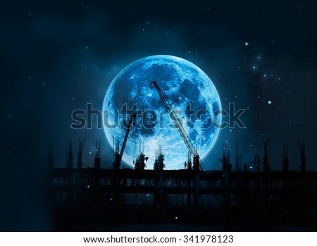 Construction site with cranes and workers full blue moon at night background, Moon original image from NASA.gov