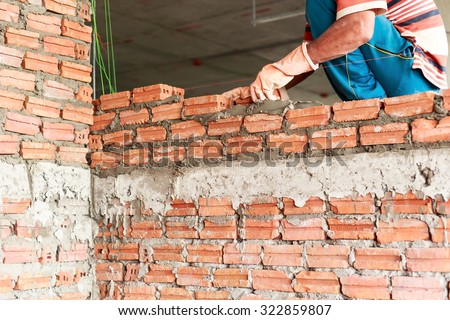 Construction worker building brick block wall on construction site.