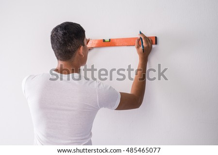 Construction worker measuring wall's straightness with spirit level