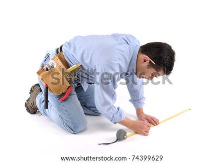 Construction worker with tool belt measuring the floor over white background - a series of MANUAL WORKER images.