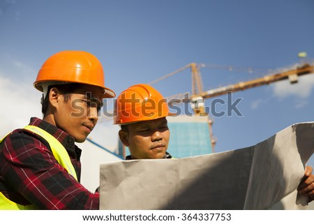 Construction workers explaining a blueprint to a worker