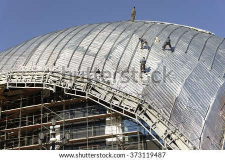 Construction workers-roofers, tied with ropes for protection work on the roof of a new building - the dome of the new building of the Philharmonic Orchestra in Skopje - Macedonia under construction 3