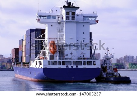 Container ship entering port helped by a tug