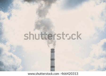 contrast silhouette of a pipe with smoke pillar of the sky with clouds