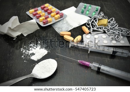 Cooked heroin on spoon and Drug syringe